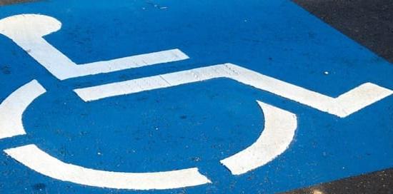 simbolo blu parcheggio disabili su asfalto