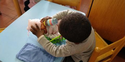 Bimbo dà il biberon alla bambola